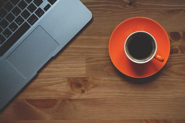 oranžový hrnek, káva, notebook